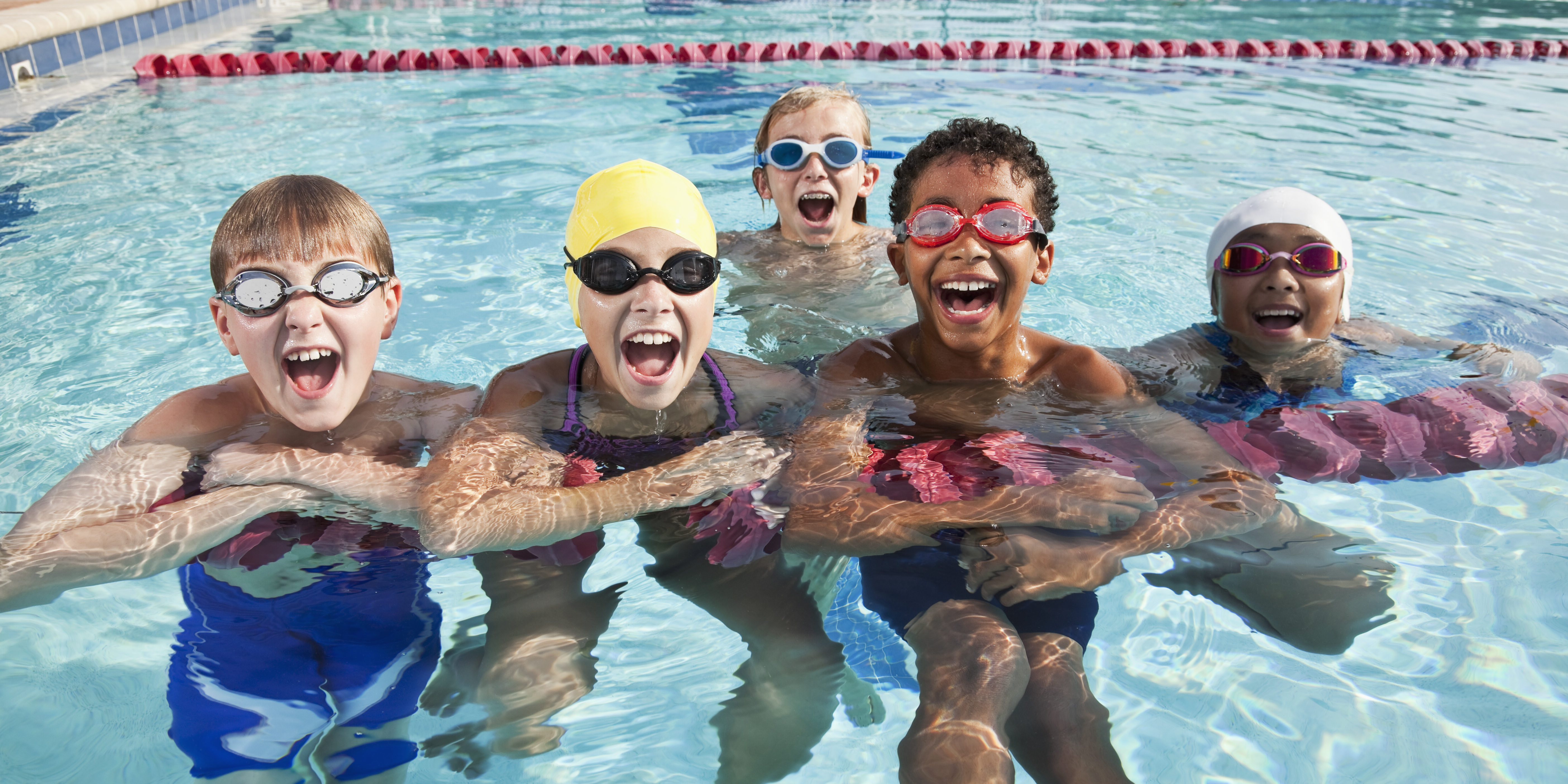 A multiracial group of five children having fun in a swimming pool, hanging onto a lane rope, looking at the camera, laughing and shouting.  The three boys and two girls are 9 to 12 years old.  They are wearing swimsuits and goggles, and the girls have on swim caps.