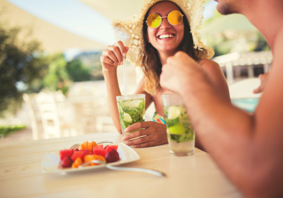 Two people having fun at the holiday resort in summer,drinking cocktails,enjoying and smiling,fruit on the table