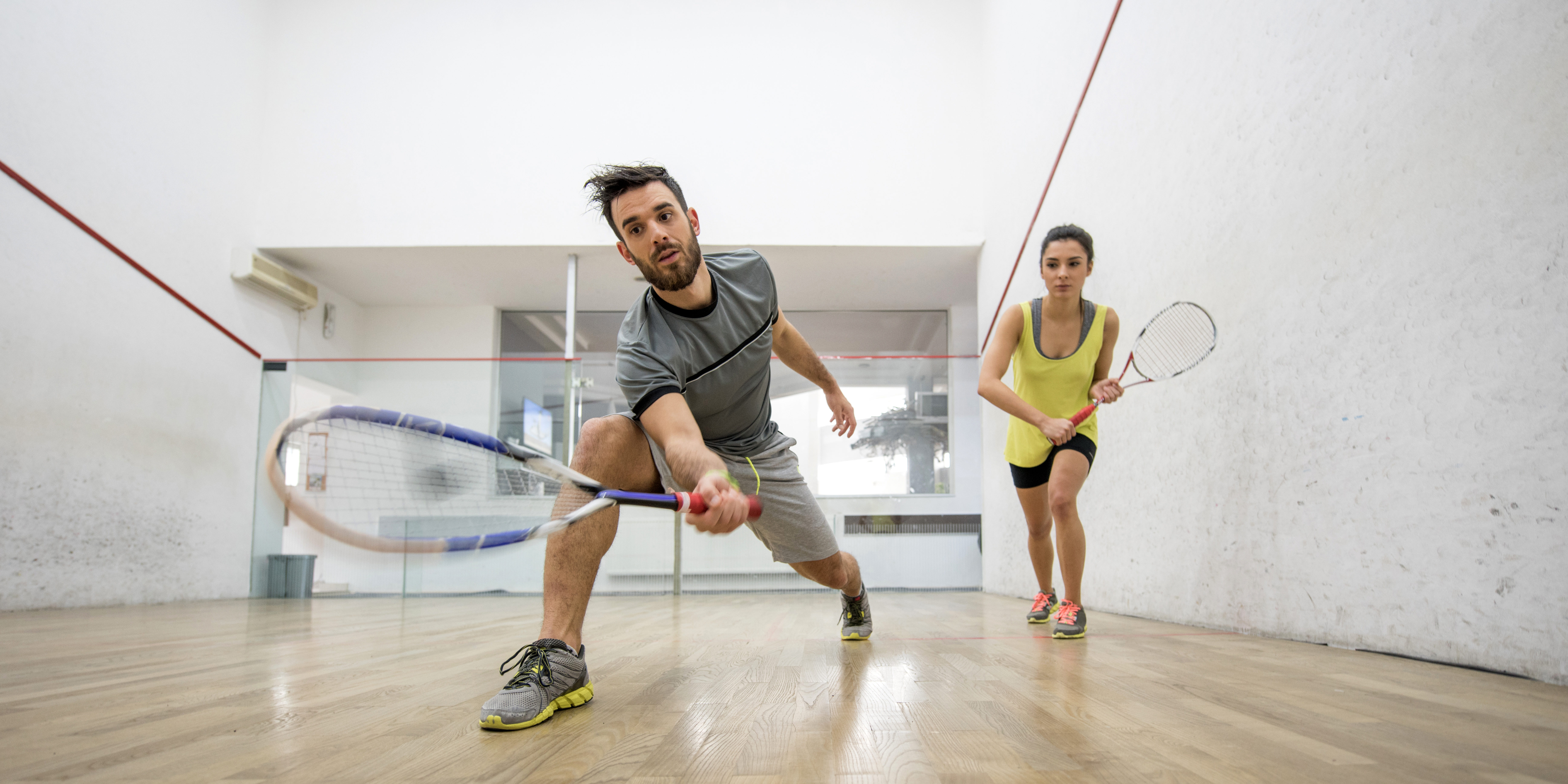 Below view of young man and woman playing squash.