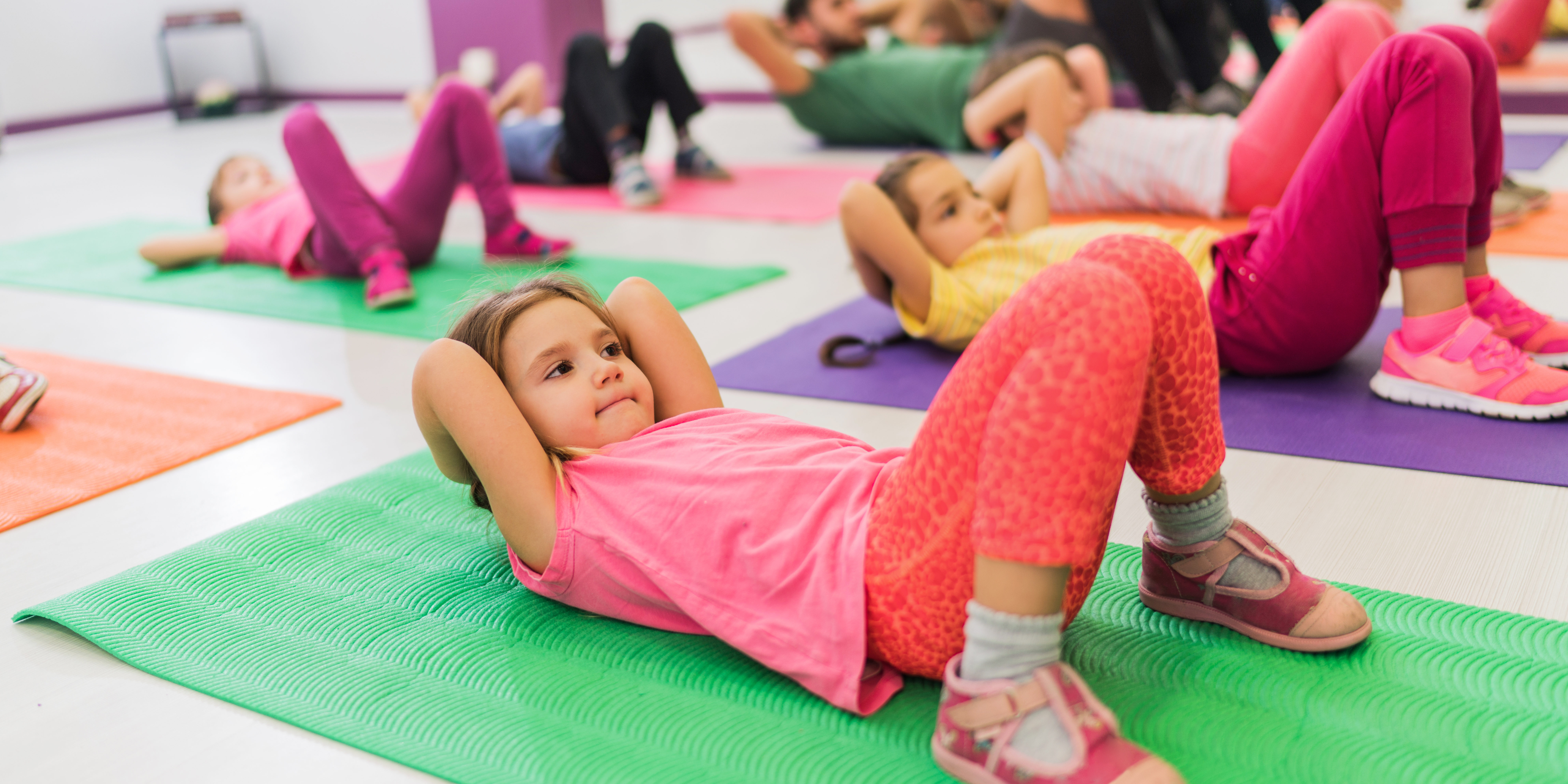 Kids doing sit-ups on a sports training in health club.
