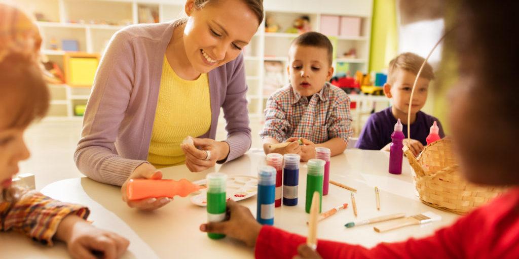 Happy preschool teacher coloring with kids in kindergarten.